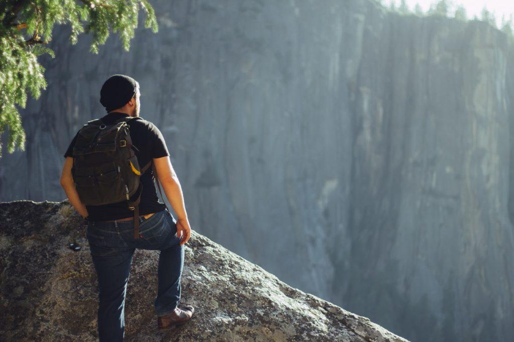 мужчина стоит на краю горы