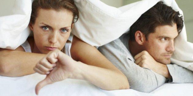 недовольные мужчина и женщина под одеялом