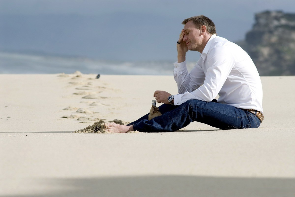 Мужчина сидит на песке на пляже