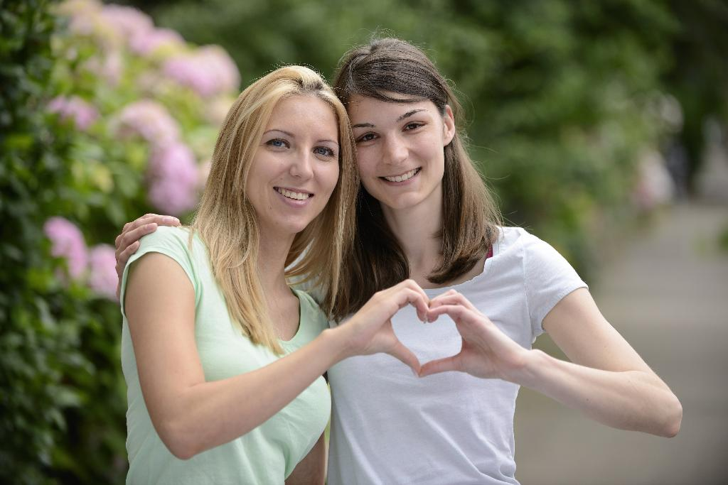две девушки сложили руки в форме сердца