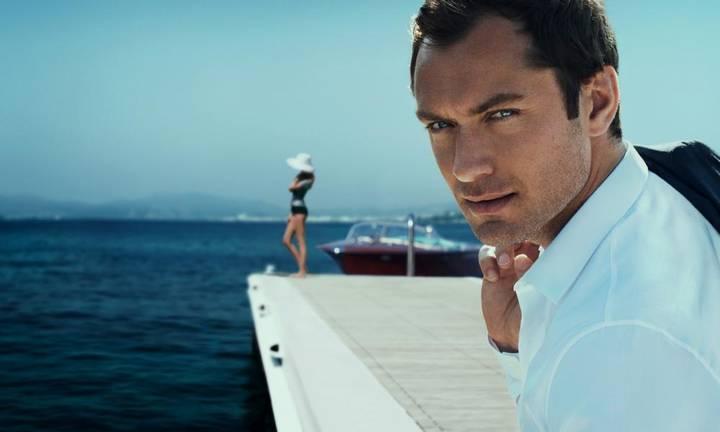 Мужчина смотрит в камеру на фоне дорогой яхты и девушки