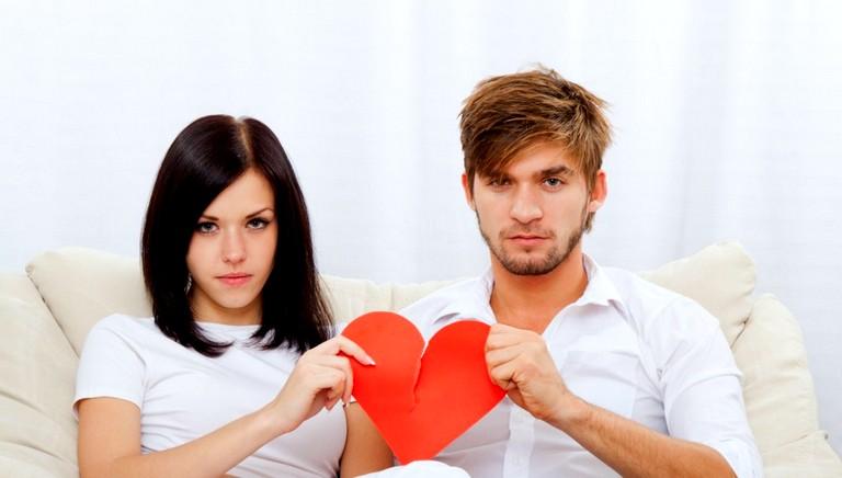 парень с девушкой держат разорванное бумажное сердце