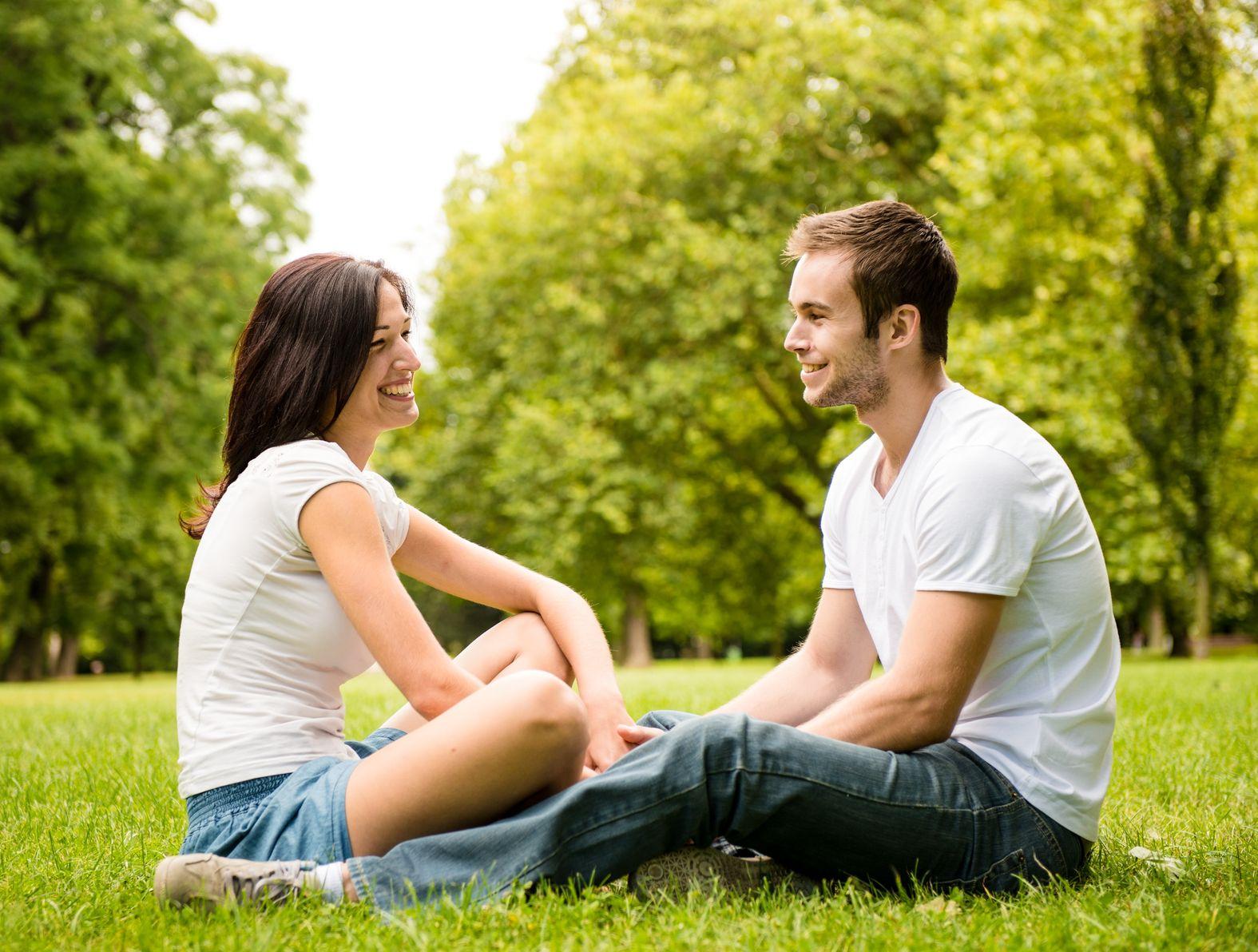 парень с девушкой сидят на земле в парке