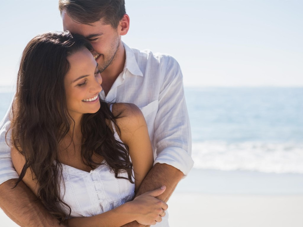 парень с девушкой обнимаются на фоне моря