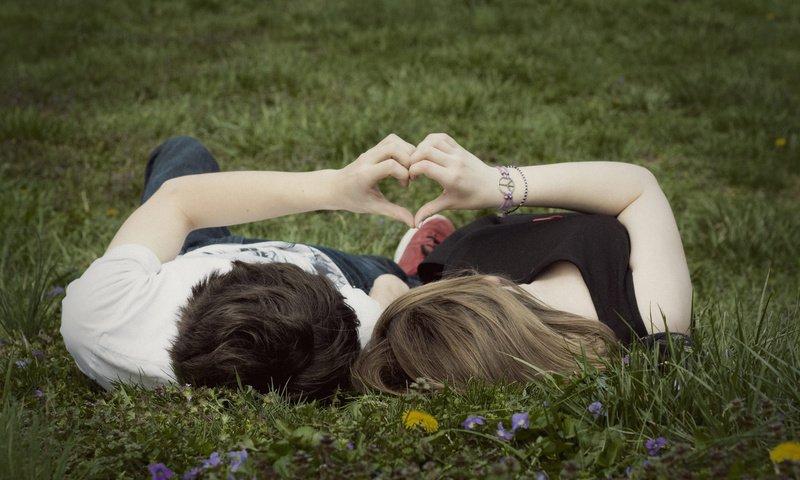 парень с девушкой сложили руки в форме сердца