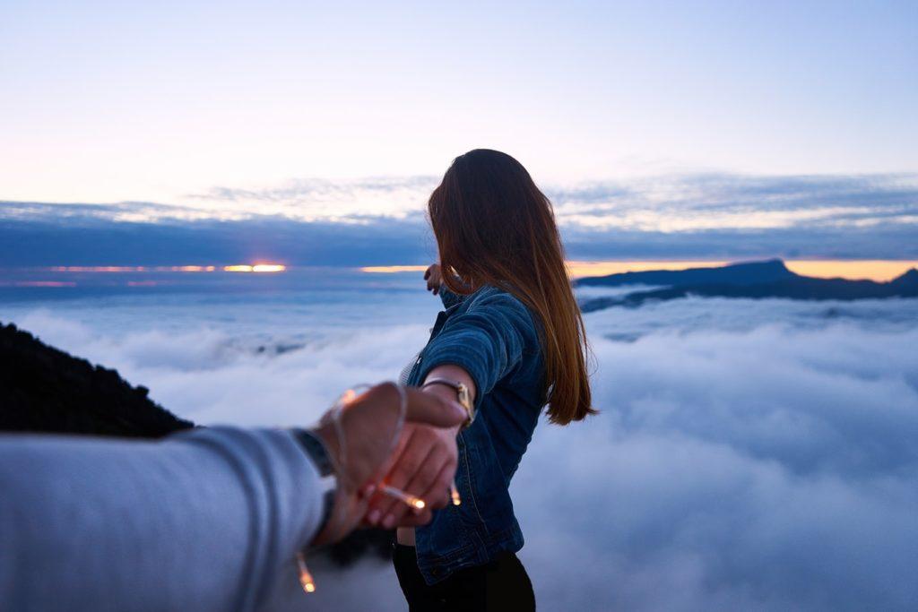 девушка держит парня за руку на фоне облаков
