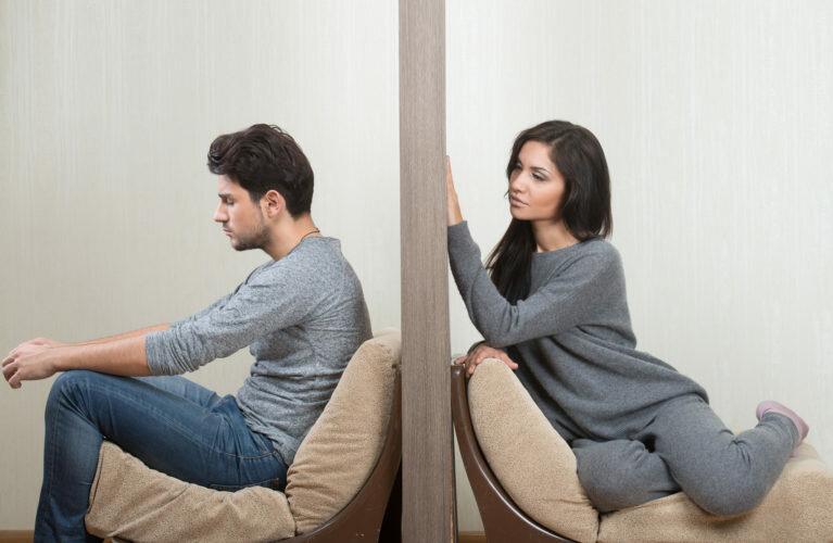 Девушка и парень сидят по разные стороны стены