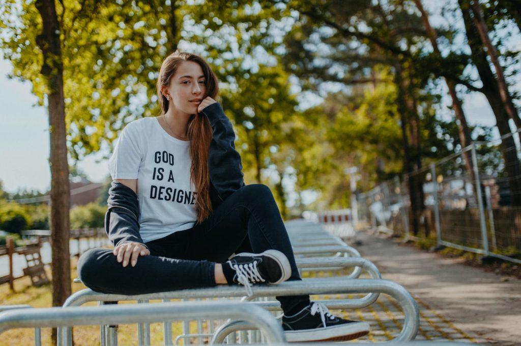 девушка сидит поверх лавочки в парке